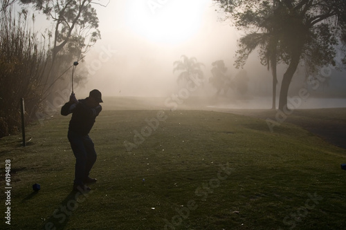 Early morning golfers silhouetted in a dense fog