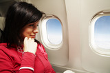 Fototapety young woman is on passanger seat at airplane