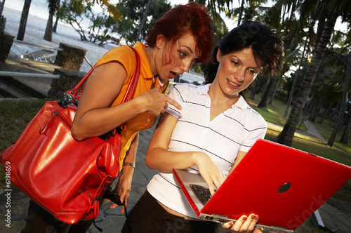 two beautiful women are working at laptop