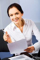 Portrait of beautiful receptionist holding a paper and pen