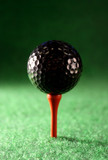 Black golfball waiting for a hungry drive