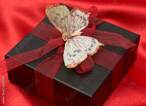 Valentines gift box with red ribbon and colorful butterfly