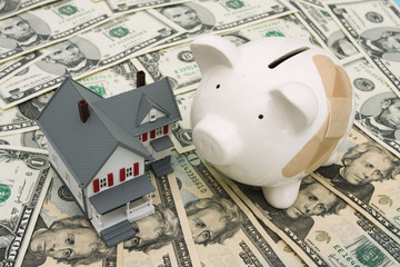Piggy bank with adhesive bandage and house