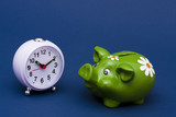 Clock with piggy bank on blue background
