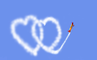 an aeroplane drawing hearts in the sky