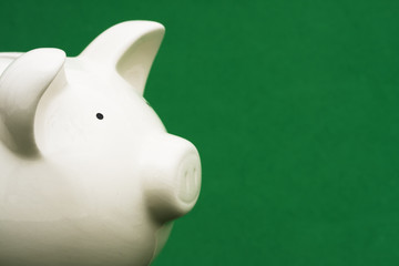 Piggy bank on green background with copy space