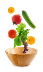 Assorted fresh vegetables falling into a wooden salad bowl