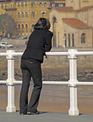 Mujer apoyada en la barandilla