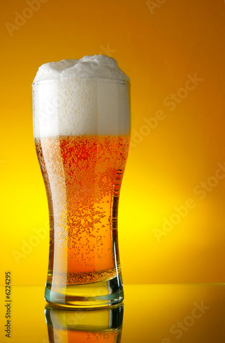 Glass of beer close-up with froth over yellow background