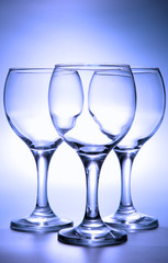 Three empty footed glasses toned in blue color