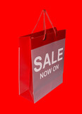 A red shopping bag with the words SALE NOW ON poster