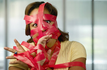 Businesswoman wrapped in red tape