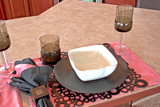 A place setting with a bowl, plate, and glasses. poster