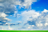 White fluffy clouds and a green spring field.. poster