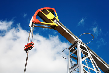 Oil pump jack against blue sky background