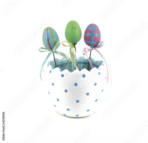 Three decorated Easter eggs in a half egg pot.
