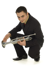 Man in suit holding a trumpet and crouching.