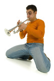 Man in orange blouse kneeling and trumpet. Low angle view.