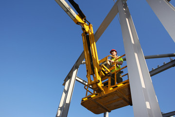 Construction worker operating cherry picker