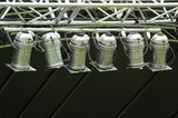 Multiple stage spotlight arrangement over black poster