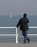 Hombre con teléfono mirando al mar poster