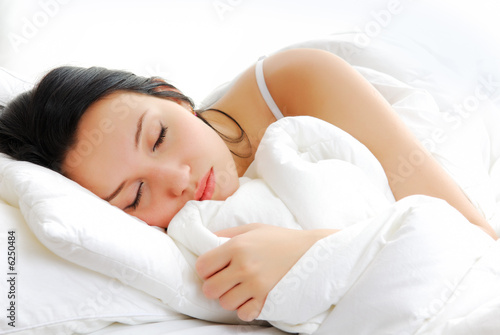 Leinwanddruck Bild Beautiful woman lying and sleep on the snowy bed