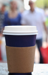 blue coffee cap with lid on a street people background