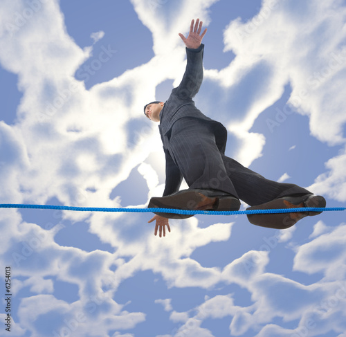Young businessman walking on line in the air.
