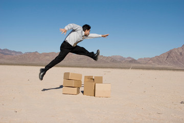 Businessman jumping over the boxes
