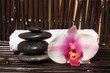 Massage stones and orchid flowers on bamboo