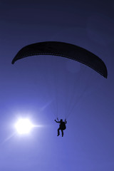 Paraglider flying on sunset