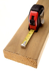Tape measure on wood over white