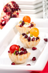 fillo shells filled with cream cheese, Pomegranates, tomatoes