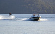 canvas print picture - waterskier jumps into air behind fast speedboat