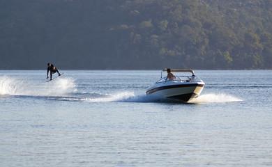 waterskier jumps into air behind fast speedboat