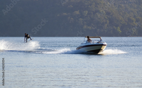 canvas print picture waterskier jumps into air behind fast speedboat