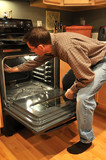 A man is cleaning the inside of the oven in a kitchen. poster