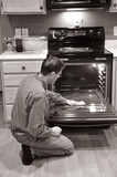 A man kneels on the floor in the kitchen and cleans the oven. poster