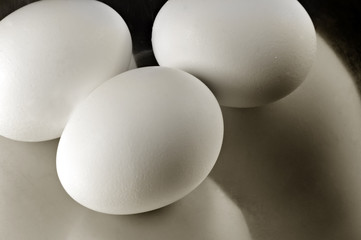 Three whole eggs on stainless steel.