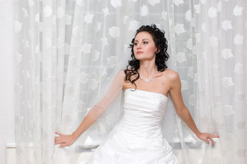 bride stands by the window