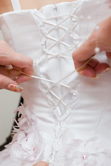 girls lace up a wedding dress of the bride