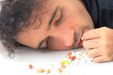 Depressed man taking capsule of drugs . poster