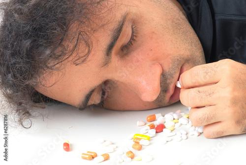 poster of Depressed man taking capsule of drugs .