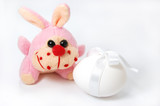 Toy bunny and white egg isolated on white