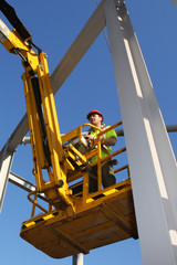 Steel worker operating a cherry picker