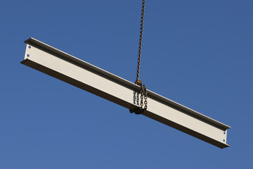Steel girder swinging from a crane on a construction site