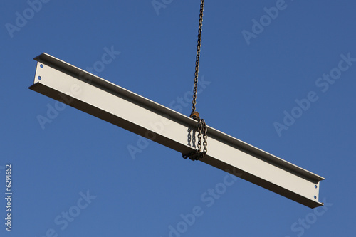 Steel girder swinging from a crane on a construction site - 6291652