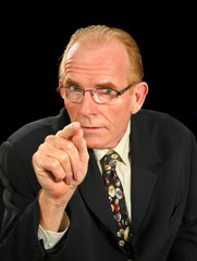 Middle aged businessman pointing in an intimidating manner.