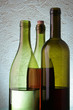 Still-life with three wine bottles over textured background