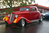 A 30s Ford hotrod with flames captured at a car show in the rain poster